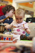 A boy plays a drum with a baby girl, Norland Nursery, Bath. - Paul Box - 2010s,2012,babies,baby,boy,BOYS,CARE,carer,carers,child,child care,childcare,CHILD-CARE,CHILDHOOD,childminding,children,CRECH,creche,creches,day care,daycare,drum,drummer,drummers,drumming,drums,EARLY