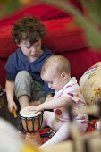 A boy plays a drum with a baby girl, Norland Nursery, Bath. - Paul Box - ,2010s,2012,babies,baby,boy,boys,CARE,carer,carers,child,child care,childcare,CHILD-CARE,CHILDHOOD,childminding,children,CRECH,creche,creches,day care,daycare,drum,drummer,drummers,drumming,drums,EARL