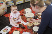 A baby plays a drum with a nursery worker, Norland Nursery, Bath. - Paul Box - 2010s,2012,attention,attentive,babies,baby,CARE,carer,carers,child,child care,childcare,CHILD-CARE,CHILDHOOD,childminding,children,class,communicating,communication,conversation,conversations,CRECH,cr