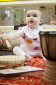 A baby plays a drum with nursery staff, Norland Nursery, Bath. - Paul Box - 2010s,2012,babies,baby,CARE,carer,carers,child,child care,childcare,CHILD-CARE,CHILDHOOD,childminding,children,CRECH,creche,creches,day care,daycare,drum,drummer,drummers,drumming,drums,EARLY,EARLY YE