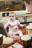 A baby playing a drum with a nursery worker, Norland Nursery, Bath. - Paul Box - 2010s,2012,babies,baby,CARE,carer,carers,child,child care,childcare,CHILD-CARE,CHILDHOOD,childminding,children,class,communicating,communication,CRECH,creche,creches,day care,daycare,drum,drummer,drum