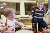 A baby plays a drum with an older boy, Norland Nursery, Bath. - Paul Box - 2010s,2012,babies,baby,boy,boys,CARE,carer,carers,child,child care,childcare,CHILD-CARE,CHILDHOOD,childminding,children,CRECH,creche,creches,day care,daycare,drum,drummer,drummers,drumming,drums,EARLY