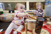 A baby plays a drum with an older boy, Norland Nursery, Bath. - Paul Box - ,2010s,2012,babies,baby,boy,boys,CARE,carer,carers,child,child care,childcare,CHILD-CARE,CHILDHOOD,childminding,children,CRECH,creche,creches,day care,daycare,drum,drummer,drummers,drumming,drums,EARL