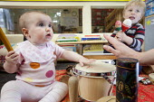 A baby playng a drum with an older boy, Norland Nursery, Bath. - Paul Box - 2010s,2012,boy,boys,CARE,carer,carers,child,child care,childcare,CHILD-CARE,CHILDHOOD,childminding,children,CRECH,creche,creches,day care,daycare,drum,drummer,drummers,drumming,drums,EARLY,early years