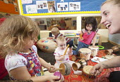 A young girl playsing a drum with older girls and a nursery worker, Norland Nursery, Bath. - Paul Box - , motivating,2010s,2012,boy,BOYS,CARE,carer,carers,child,child care,childcare,CHILDHOOD,childminding,children,children child,creche creches,day care,daycare,drummer,drummers,drumming drum drums,early
