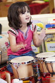 A young girl playing a drum Norland Nursery, Bath. - Paul Box - 2010s,2012,boy,BOYS,CARE,carer,carers,child,child care,childcare,CHILD-CARE,CHILDHOOD,childminding,children,CRECH,creche,creches,day care,daycare,drum,drummer,drummers,drumming,drums,EARLY,early years
