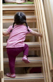 A young girl climbing the stairs, Norland Nursery, Bath. - Paul Box - 2010s,2012,CARE,carer,carers,child,child care,childcare,CHILD-CARE,CHILDHOOD,childminding,children,climb,climbed,climbing,CRECH,creche,creches,day care,daycare,EARLY,early years,edu,educate,educating,