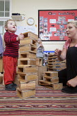A young boy playing with wooden blocks and a Nursery worker, Norland Nursery, Bath. - Paul Box - 2010s,2012,boy boys,CARE,carer,carers,child,child care,childcare,CHILDHOOD,childminding,children,children child,creche creches,day care,daycare,early years,edu education,employee,employees,Employment,
