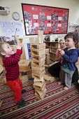 A young boy playing with wooden blocks and a Nursery worker, Norland Nursery, Bath. - Paul Box - 2010s,2012,blocks,boy,boys,CARE,carer,carers,child,child care,childcare,CHILD-CARE,CHILDHOOD,childminding,children,class,communicating,communication,CRECH,creche,creches,day care,daycare,EARLY,early y