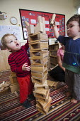 A young boy playing with wooden blocks, Norland Nursery, Bath. - Paul Box - 2010s,2012,boy boys,CARE,carer,carers,child,child care,childcare,CHILDHOOD,childminding,children,children child,creche creches,day care,daycare,early years,edu,educate,educating,education,educational,