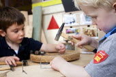 A young boy using a hammer and nails, Norland Nursery, Bath. - Paul Box - 2010s,2012,boy,boys,CARE,carer,carers,child,child care,childcare,CHILD-CARE,CHILDHOOD,childminding,children,CRECH,creche,creches,day care,daycare,EARLY,early years,edu,educate,educating,education,educ