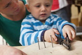 A young boy using pliers and nails with encouragement from a nursery worker. Norland Nursery, Bath. - Paul Box - 2010s,2012,boy,boys,CARE,carer,carers,child,child care,childcare,CHILD-CARE,CHILDHOOD,childminding,children,class,communicating,communication,CRECH,creche,creches,day care,daycare,EARLY,early years,ed