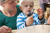 A young boy using pliers and nails with encouragement from a nursery worker. Norland Nursery, Bath. - Paul Box - 2010s,2012,attention,attentive,boy,boys,CARE,carer,carers,child,child care,childcare,CHILD-CARE,CHILDHOOD,childminding,children,class,communicating,communication,conversation,conversations,CRECH,crech