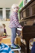 A young boy playing a piano, Norland Nursery, Bath. - Paul Box - 2010s,2012,boy,boys,CARE,carer,carers,child,child care,childcare,CHILD-CARE,CHILDHOOD,childminding,children,CRECH,creche,creches,day care,daycare,EARLY,early years,edu,educate,educating,education,educ