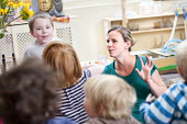 Nursery worker telling a story to a mixed age group of young children, Norland Nursery, Bath. - Paul Box - 2010s,2012,age,at,attention,attentive,boy,boys,CARE,carer,carers,child,child care,childcare,CHILD-CARE,CHILDHOOD,childminding,children,class,communicating,communication,CRECH,creche,creches,day care,d