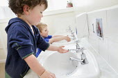 A young boy washing his hands in the toilet, Norland Nursery, Bath. - Paul Box - 2010s,2012,boy,boys,CARE,carer,carers,child,child care,childcare,CHILD-CARE,CHILDHOOD,childminding,children,CRECH,creche,creches,day care,daycare,EARLY,early years,edu,educate,educating,education,educ