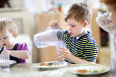 A young boy pouring water from a jug into a glass, Norland Nursery, Bath. - Paul Box - 2010s,2012,CARE,carer,carers,child,child care,childcare,CHILD-CARE,CHILDHOOD,childminding,children,CRECH,creche,creches,day care,daycare,drink,drinker,drinkers,drinking,drinks,EARLY,early years,edu,ed