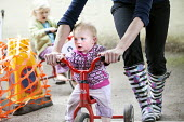 Children playing on tricycles outside, Norland Nursery, Bath. - Paul Box - 2010s,2012,areas,bicycle,bicycles,BICYCLING,Bicyclist,Bicyclists,BIKE,BIKES,CARE,carer,carers,child,child care,childcare,CHILD-CARE,CHILDHOOD,childminding,children,CRECH,creche,creches,cycle,cycles,cy