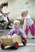 Children playing on tricycles outside, Norland Nursery, Bath. - Paul Box - ,2010s,2012,areas,bicycle,bicycles,BICYCLING,Bicyclist,Bicyclists,BIKE,BIKES,CARE,carer,carers,child,child care,childcare,CHILD-CARE,CHILDHOOD,childminding,children,CRECH,creche,creches,cycle,cycles,c
