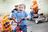 Children playing on tricycles outside, Norland Nursery, Bath. - Paul Box - 2010s,2012,areas,bicycle,bicycles,BICYCLING,Bicyclist,Bicyclists,BIKE,BIKES,boy,boys,CARE,carer,carers,child,child care,childcare,CHILD-CARE,CHILDHOOD,childminding,children,CRECH,creche,creches,cycle,