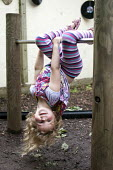 A girl playing outside on a climbing frame, Norland Nursery, Bath. - Paul Box - ,2010s,2012,areas,CARE,carer,carers,child,child care,childcare,CHILD-CARE,CHILDHOOD,childminding,children,climb,climbed,climbing,CRECH,creche,creches,day care,daycare,down,EARLY,early years,edu,educat