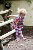 A girl playing outside on a climbing frame, Norland Nursery, Bath. - Paul Box - 2010s,2012,areas,CARE,carer,carers,child,child care,childcare,CHILD-CARE,CHILDHOOD,childminding,children,climb,climbed,climbing,CRECH,creche,creches,day care,daycare,EARLY,early years,edu,educate,educ