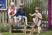 Boys playing outside on wooden boxes in discussion, Norland Nursery, Bath. - Paul Box - ,2010s,2012,areas,box,boxes,boy,boys,CARE,carer,carers,child,child care,childcare,CHILD-CARE,CHILDHOOD,childminding,children,communicating,communication,conversation,conversations,CRECH,creche,creches