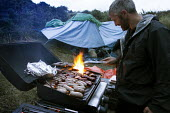 An outdoor activities organiser cooking on a barbecue for a stag party who are staying overnight in the dunes at Poppit sands, Cardigan, Pembrokeshire, Wales. - Paul Box - 07-09-2013