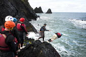 A stag party coasteering, exploring a rocky coastline, Moylegrove, Cardigan, Pembrokeshire, Wales. - Paul Box - 08-09-2013