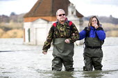 Residents of Windsor, Berkshire which has been flooded after the Thames burst its banks wade through flood waters. - Paul Box - 13-02-2014