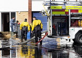A resident brings tea and biscuits to firefighters to have a break. Firefighters pump water from flooded properties in Datchet , Berkshire which has been flooded after the Thames burst its banks. - Paul Box - 13-02-2014