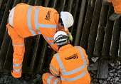Network rail workers clean up after the railway line flooded in Datchet , Berkshire which has been flooded after the Thames burst its banks. - Paul Box - 2010s,2014,arse,BAD,BUILDER,builders,bum,CLIMATE,Climate Change,conditions,crack,DIA,employee,employees,Employment,eni,environment,Environmental Issues,EXTREME,flood,flooded,flooding,floods,Global War