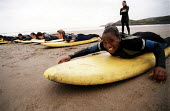 School leavers learning to surf on a Connexions and Youth Service outdoor activity challenge, St David's Head South Wales. - Paul Box - 2000,2000s,activities,adolescence,adolescent,adolescents,BAME,BAMEs,beach,beaches,black,BME,bmes,board,boards,child,CHILDHOOD,children,COAST,coastal,coasts,diversity,edu,EDU education,educate,educatin
