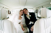 Bride and groom arrive at their wedding in a limousine - Paul Box - 2000s,2002,adult,adults,and,AUTO,AUTOMOBILE,AUTOMOBILES,AUTOMOTIVE,brides,Car,cars,couple,COUPLES,EMOTION,EMOTIONAL,EMOTIONS,FEMALE,Getting Married,happiness,happy,LFL,LIFE,Lifestyle,limousine,limousi