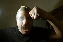 Man wearing stocking on head looking aggressive - Paul Box - 01-11-2003
