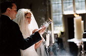 Bride and groom sing hymns during their wedding ceremony, Essex. - Paul Box - 20-06-2002