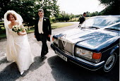 Bride and bridesfather arrive at wedding ceremony in Essex - Paul Box - 2000s,2002,AUTO,AUTOMOBILE,AUTOMOBILES,AUTOMOTIVE,away,bride,brides,car,CARS,ceremonies,ceremony,church,churches,DAD,DADDIES,DADDY,DADS,day,Essex,excited,father,FATHERHOOD,FATHERS,FLOWER,flowering,flo