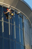 Window cleaner working off ropes on very high office building, Bristol. - Paul Box - 28-11-2003