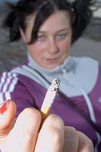 Young woman holding up a cigarette. - Paul Box - 01-11-2003