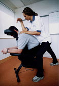 Stressed office workers get a massage from occupational physiotherapist, to try and avoid health and safety issues or loss of productivity through time off. - Paul Box - 14-07-2002