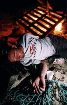 A drunken man falls asleep at a beach fire - Paul Box - 01-10-2003