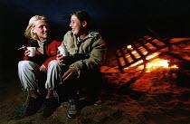 Good friends talking at a beach party. - Paul Box - 01-10-2003