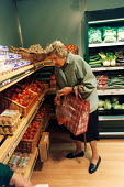 An elderly woman shops for fruit and veg at a grocery store, Bath. - Paul Box - 01-11-2003