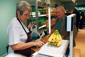An elderly woman serving at fruit and veg store or grocery store. - Paul Box - 01-11-2003