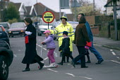 A lollipop lady escorts children accross the road with her stop sign. Outside a school, Bristol - Paul Box - 04-12-2003