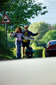 Students hitch hiking to Glastonbury Festival. - Paul Box - ,2000s,2001,a,AUTO,AUTOMOBILE,AUTOMOBILES,AUTOMOTIVE,car,cars,FEMALE,festival,FESTIVALS,goer,hiker,hikers,hiking,hitch,hitching,holiday,holiday maker,holiday makers,holidaymaker,holidaymakers,HOLIDAYS