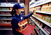 Young worker filling the shelves in a convenience store Bristol - Paul Box - 14-07-2002