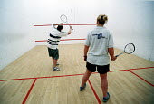 Competitors playing squash. Axa Sun Life. Bristol. - Paul Box - ,2000s,2002,cardio vascular,Cardiovascular,centre,cities,city,club,clubs,COMPETITATIVE,Competition,Competitive,Competitor,exercise,exercises,exercising,FEMALE,fit,fitness,game,games,get,getting,health