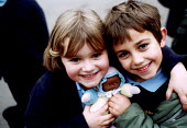 Pupils sharing a toy doll in the playground at Bruton Primary School Somerset. - Paul Box - 14-07-2000
