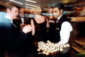 Waiters serving passengers with appetizers and snacks. P&O cruises Ship Aurora, a 76,000 ton cruiser in dock. It can carry 1800 passengers. Southampton. The crew is mostly Indonesian. - Paul Box - 14-05-2002